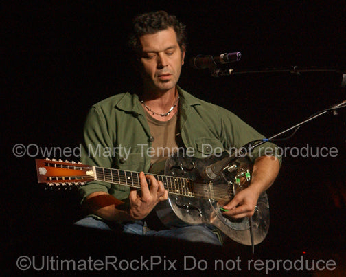 Photo of Doyle Bramhall II playing a 12 string resonator guitar in concert in 2010 by Marty Temme