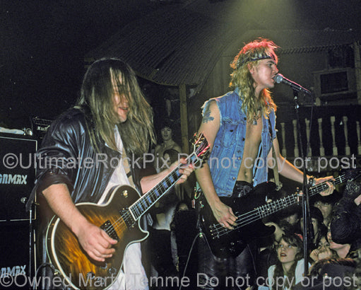 Photo of West Arkeen and Duff McKagan in concert in 1990 by Marty Temme