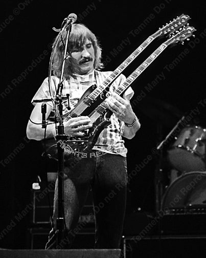 Black and white photo of Joe Walsh of The Eagles playing a doubleneck SG in concert in 1980 by Marty Temme