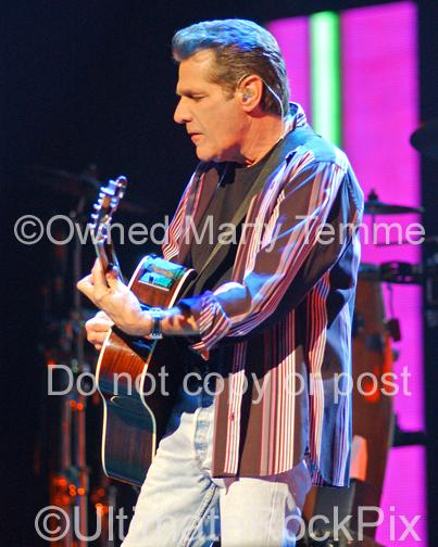 Photo of Glenn Frey of The Eagles playing acoustic guitar in concert by Marty Temme