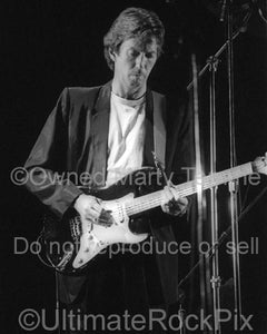 Photo of Eric Clapton playing his black Stratocaster with Roger Waters in concert 1984 by Marty Temme