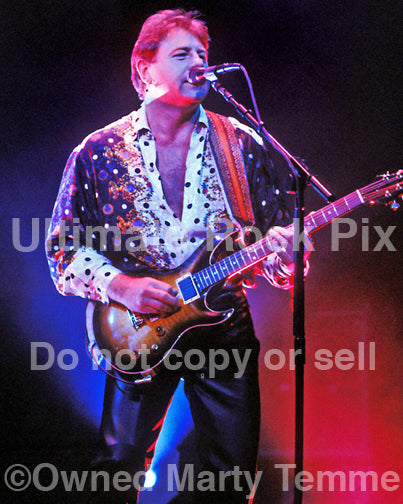 Photo of Greg Lake of Emerson, Lake & Palmer playing a PRS guitar in concert in 1992 by Marty Temme