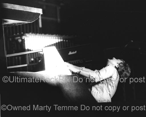 Photo of Keith Emerson of Emerson, Lake and Palmer playing the organ in concert in 1977 by Marty Temme