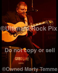 Photos of Greg Lake of Emerson, Lake and Palmer and King Crimson playing an Acoustic Gibson Guitar in Concert in 2012 by Marty Temme