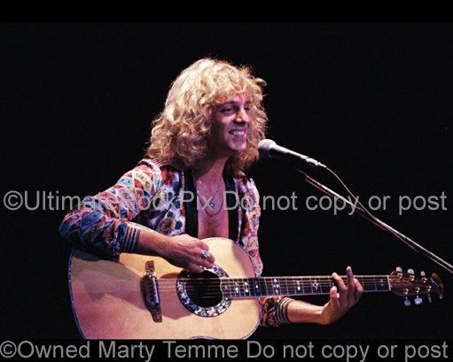 Photo of Peter Frampton playing acoustic guitar in concert in 1974 by Marty Temme
