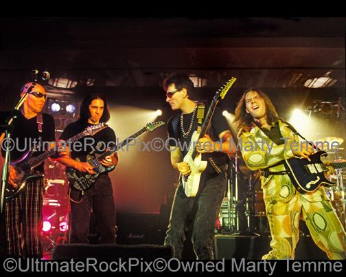 Photos of Guitar Players Joe Satriani, John Petrucci, Steve Vai and Paul Gilbert Performing Together Live in Concert in 1998 in Los Angeles, California by Marty Temme