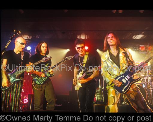 Photos of Guitar Players Joe Satriani, John Petrucci, Steve Vai and Paul Gilbert Playing Together Live in Concert in 1998 in Los Angeles, California by Marty Temme