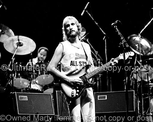Photo of Mike Rutherford of Genesis onstage in 1977 by Marty Temme