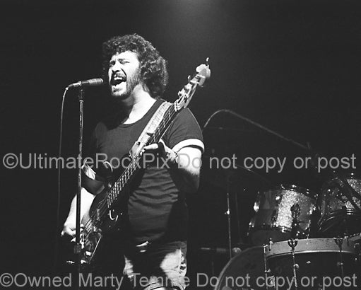 Photo of musician Derek Shulman of Gentle Giant in concert in 1980 by Marty Temme
