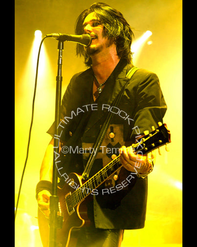 Photo of guitarist Gilby Clarke playing a Les Paul in concert by Marty Temme