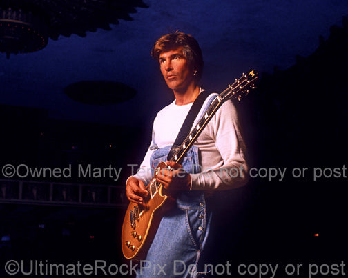 Photo of George Lynch holding a Les Paul during a photo shoot in 1995 by Marty Temme