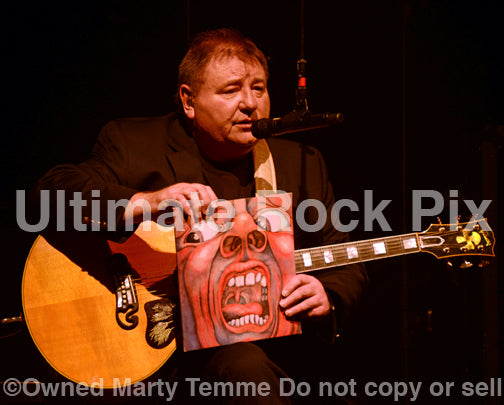 Photo of Greg Lake of Emerson, Lake and Palmer holding an album cover in concert in 2012 by Marty Temme