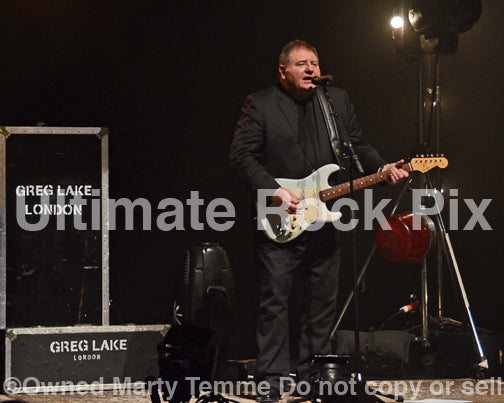Photo of Greg Lake singing and playing a Fender Stratocaster in concert in 2012 by Marty Temme