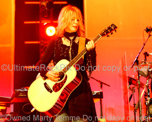Photo of Nancy Wilson of Heart playing acoustic guitar in concert by Marty Temme