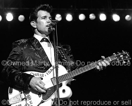 Photo of Chris Isaak playing a hollow body Gibson guitar in concert by Marty Temme