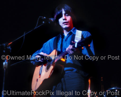 Photo of Jackson Browne playing acoustic guitar in concert in 1974 - jacksonb7414