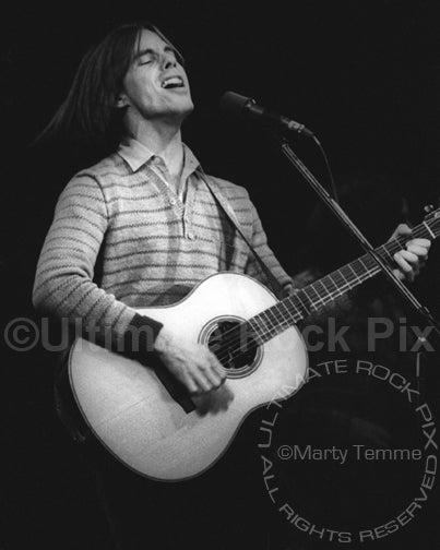 Photo of Jackson Browne playing acoustic guitar in concert in 1978 by Marty Temme