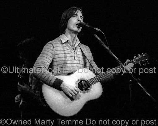 Photo of musician Jackson Browne playing acoustic guitar in concert in 1978 by Marty Temme