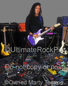 Photo of Jake E. Lee standing with his collection of guitar effects during a photo shoot in 1995 by Marty Temme