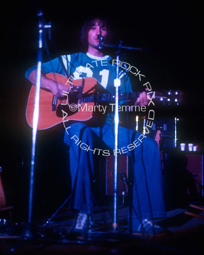 Photo of Jim Messina of Loggins and Messina playing acoustic guitar in 1973 by Marty Temme