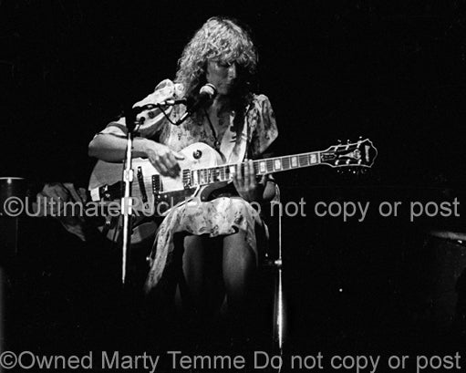 Black and white photo of Joni Mitchell playing guitar in concert in 1979 by Marty Temme