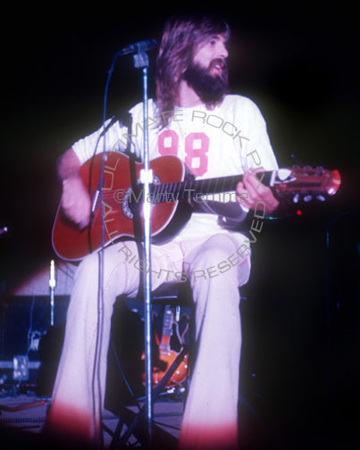 Photo of Kenny Loggins of Loggins and Messina playing an acoustic guitar in concert in 1973 by Marty Temme