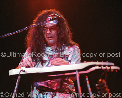 Photo of musician David Lindley playing lap steel guitar in concert by Marty Temme