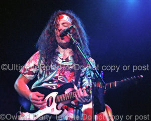Photo of musician David Lindley playing a Sears Silvertone guitar in concert by Marty Temme