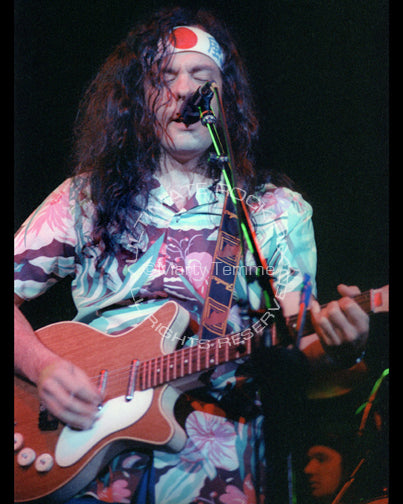 Photo of musician David Lindley playing a Danelectro guitar in concert in 1981 by Marty Temme