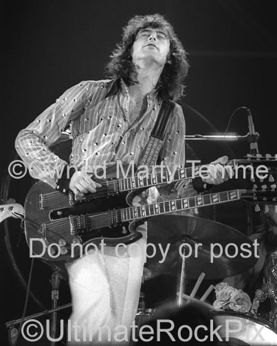Black and white photo of Jimmy Page playing a doubleneck in 1973 by Marty Temme
