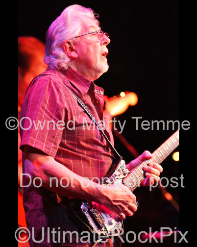Photo of blues legend John Mayall playing guitar in concert in 2008 by Marty Temme