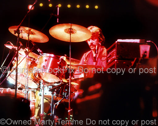 Photo of drummer Michael Botts playing with Andrew Gold in concert in 1976 by Marty Temme