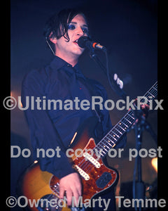 Photo of guitar player Brian Molko playing a Fender Jaguar in concert by Marty Temme
