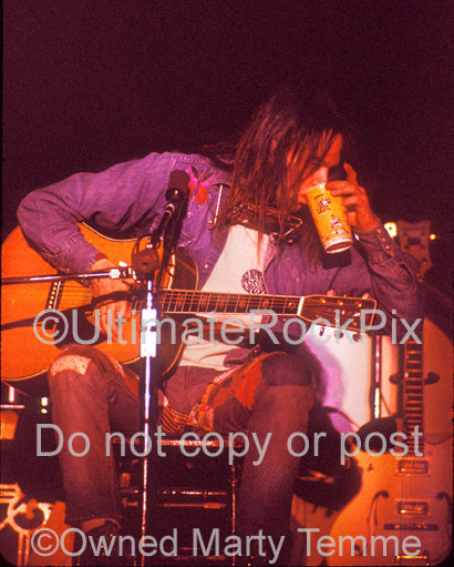 Photo of Neil Young playing his Martin in concert in 1973 by Marty Temme