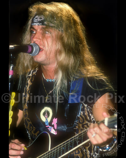 Photo of Bret Michaels of Poison playing guitar in concert in 1990 by Marty Temme