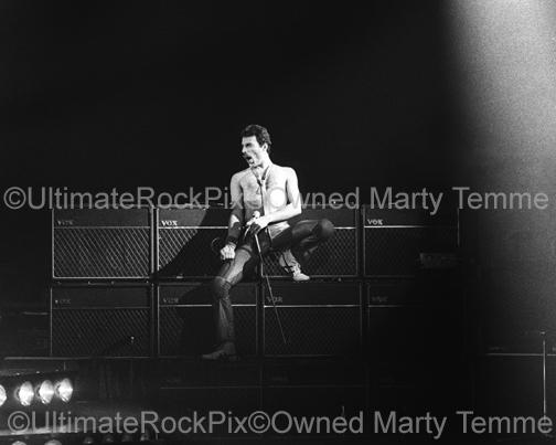 Photo of Freddie Mercury of Queen leaning on Brian May's Vox amplifiers in concert in 1980 by Marty Temme