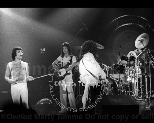 Photo of Freddie Mercury, Brian May, Roger Taylor and John Deacon of Queen in concert in 1977 by Marty Temme