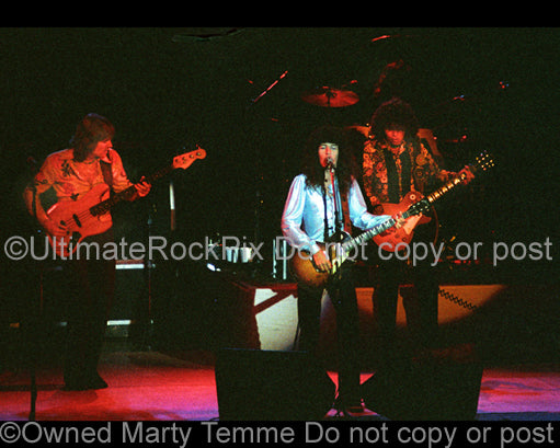 Photo of Kevin Cronin, Bruce Hall and Gary Richrath of REO Speedwagon in concert in 1977 by Marty Temme