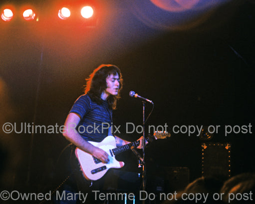 Photo of guitarist Rory Gallagher playing his Telecaster in concert in 1973 by Marty Temme