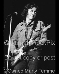 Black and white photo of Rory Gallagher playing his Stratocaster in concert in 1973 by Marty Temme
