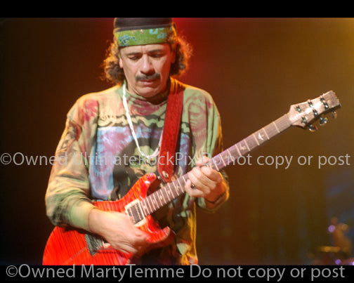 Photo of Carlos Santana of Santana playing a PRS guitar in 1999 by Marty Temme