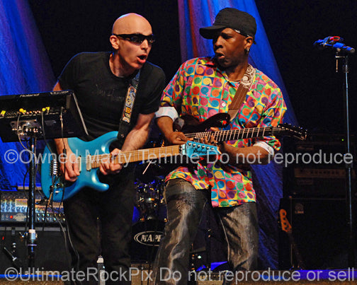 Photo of Joe Satriani and Vernon Reid of Living Colour playing together onstage by Marty Temme