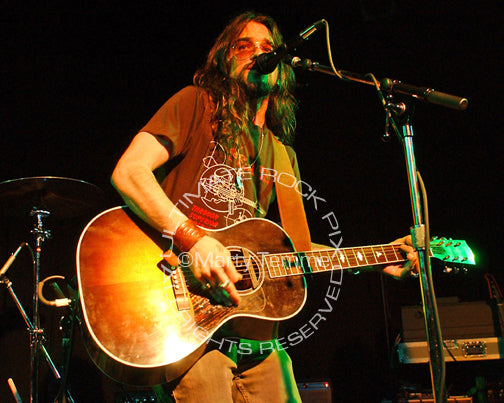 Photo of Shooter Jennings playing acoustic guitar in concert by Marty Temme