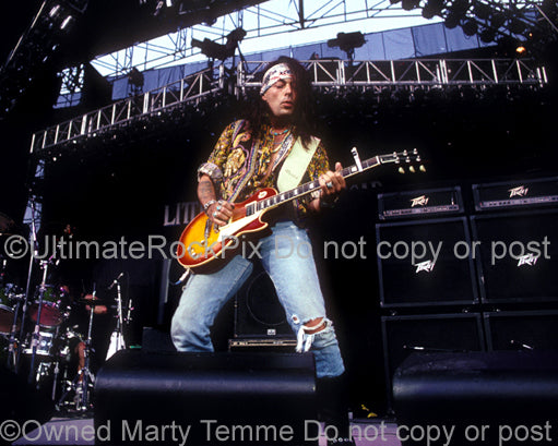 Photo of Earl Slick playing a Les Paul in concert in 1991 by Marty Temme