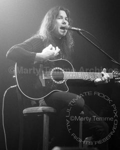 Black and white photo of Mark Slaughter playing acoustic guitar in concert by Marty Temme