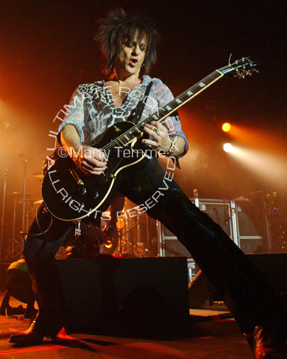 Photo of Steve Stevens playing a Les Paul in concert by Marty Temme