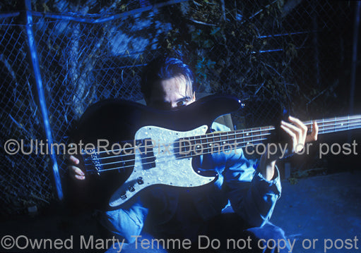 Photo of Robert DeLeo of Stone Temple Pilots holding his bass guitar during a photo shoot by Marty Temme
