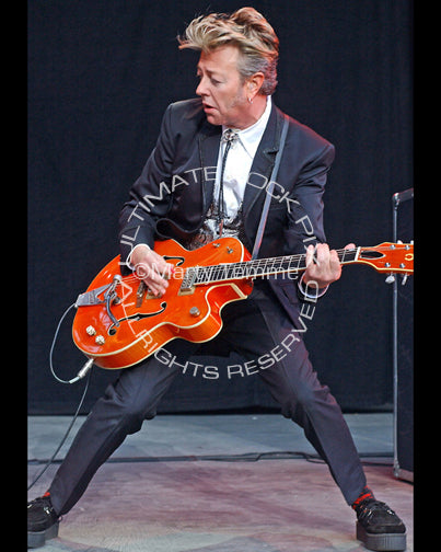 Photo of Brian Setzer of The Stray Cats playing his signature Gretsch guitar in concert by Marty Temme