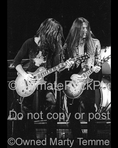 Photo of Gary Moore and Scott Gorham of Thin Lizzy in concert in 1977 by Marty Temme