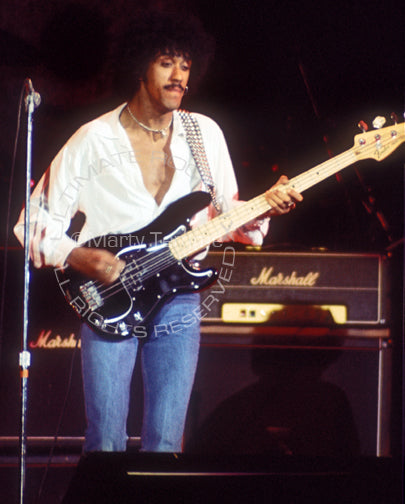Photo of Phil Lynott of Thin Lizzy in concert in 1977 by Marty Temme